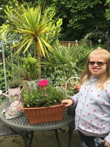 Club Member, Cerys, next to a plant bought at the Plant, Cake, Craft, and Book Sale